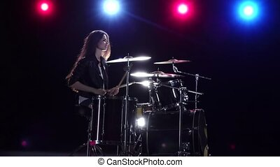 Girl drummer with chopsticks beats rhythmic music. Black background . Red light blue. Side view. Slow motion