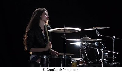 Girl drummer with chopsticks beats rhythmic music. Black...