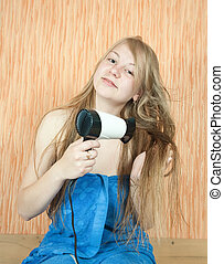 Girl dryes her long hair