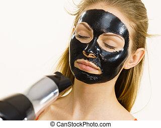 Girl drying peel-off black mask on face