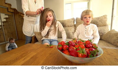 girl eat strawberry while mother comb hair and brother. red ripe berries in dish