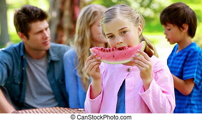 Girl eating a watermelon with her family in background in a...