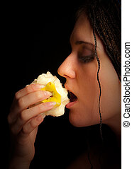 girl eating apple over the black background
