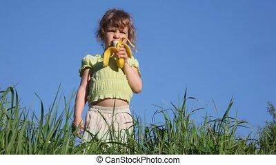 girl eating  banana in grass