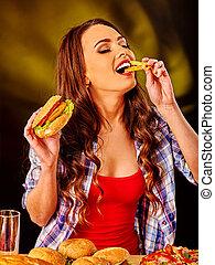 Girl eating big sandwich and fried potatoes. - Girl eats...
