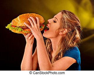 Girl eating big sandwich.