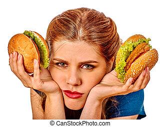 Girl eating big sandwich. - Upset girl holding two big...
