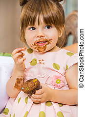 Girl Eating Birthday Cake With Icing On Her Face - Cute girl...