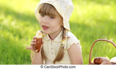 Girl eating bread. Nearby is a bask