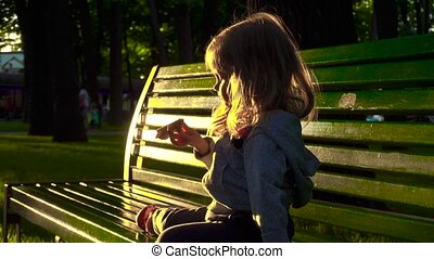 Girl eating candy on bench