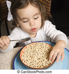 Girl eating cereal. - Caucasian girl eating bowl of cereal.