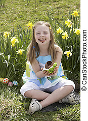 Girl Eating Chocolate Egg On Easter Egg Hunt In Daffodil Field