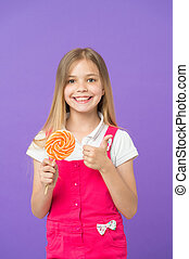 Girl eating colorful lollipop. Sweet childhood concept. Kid with long hair likes sweets. Girl with smiling face holds giant candy in hand, violet background. Child in pink overalls showing thumb up
