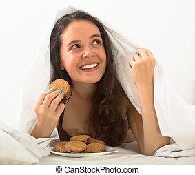 Girl eating cookies in bed