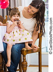 Girl Eating Cupcake While Sitting On Mother's Lap