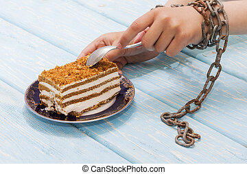 girl eating delicious cake on light blue background. Hands tied with chains.