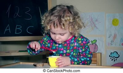 girl eating favorite yogurt with spoon. Child lick plastic spoon with tongue