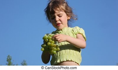 girl eating grapes in grass