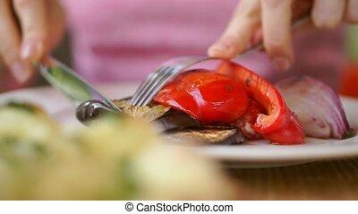 Girl eating grilled vegetables. Shallow focus close up shot...