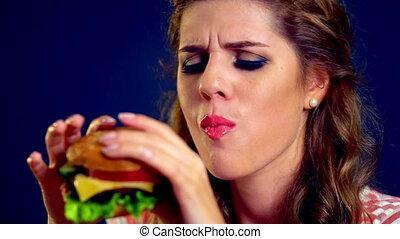 Girl eating hamburger. Girl with a big appetite eats tasty...