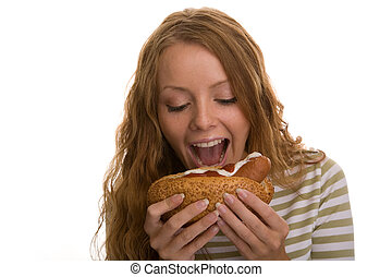 girl eating hot dog - red-haired girl eating a hot dog on a...