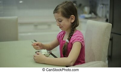 Girl eating ice cream in the kitchen