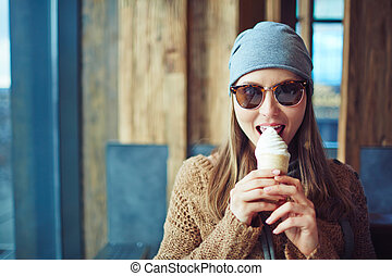 Girl eating ice-cream - Stylish girl eating ice-cream in...