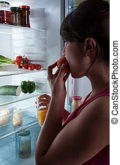 Girl eating peach and looking into the fridge