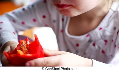 Girl eating pepper paprika, close-up.