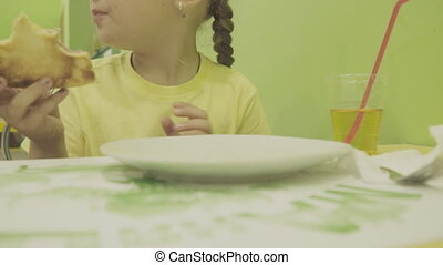 girl eating pizza - little girl is eating pizza at a...