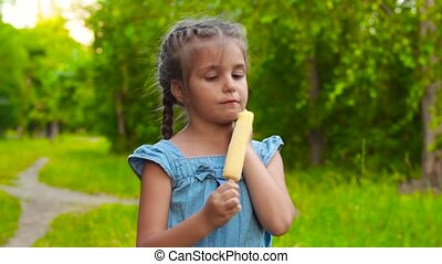 Girl eating popsicle ice-cream in park - Adorable little...