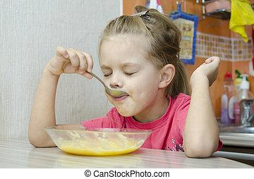Girl eating porridge in the kitchen
