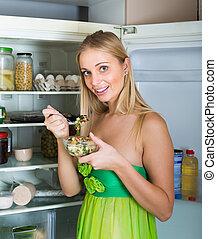 Girl eating salad from fridge
