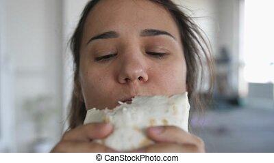 Girl eating sandwich, enjoying taste, cheap delicious but unhealthy food closeup