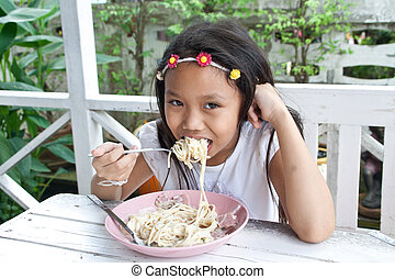 Girl eating spaghetti.