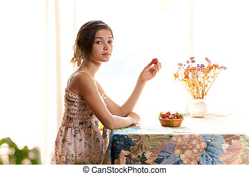Girl eating strawberries sitting at table indoor in summer day