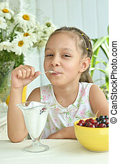 Girl eating sweet  dessert with berries