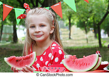 Girl eating watermelon in the garden