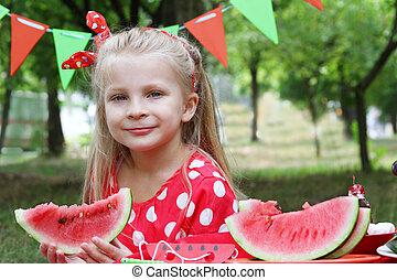 Girl eating watermelon in the garden