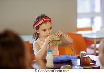 Girl eating yummy sandwich with lettuce in canteen