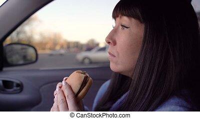 Girl eats a cheeseburger in a car