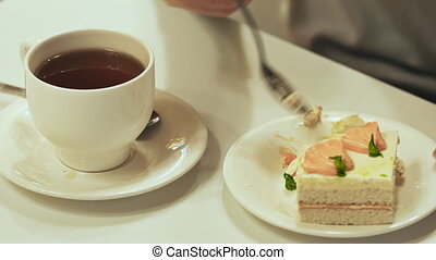Girl eats cake and tea drinks on the white table
