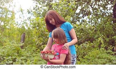 Girl eats strawberry.