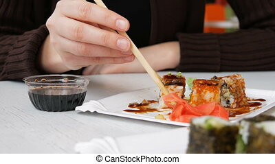 Girl Eats Sushi Rolls with Chopsticks in a Japanese Restaurant