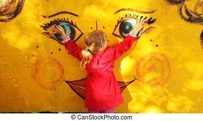 girl embraces and irons the face on a wall