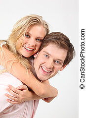 girl embraces young man for neck behind