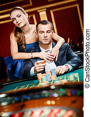 Girl embracing gambler at the roulette table