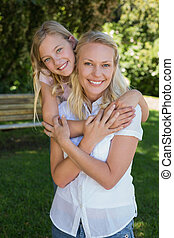 Girl embracing mother from behind in park