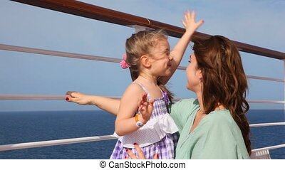 girl embracing mother on deck
