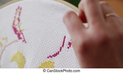 Girl embroiders with colored thread. Close-up.